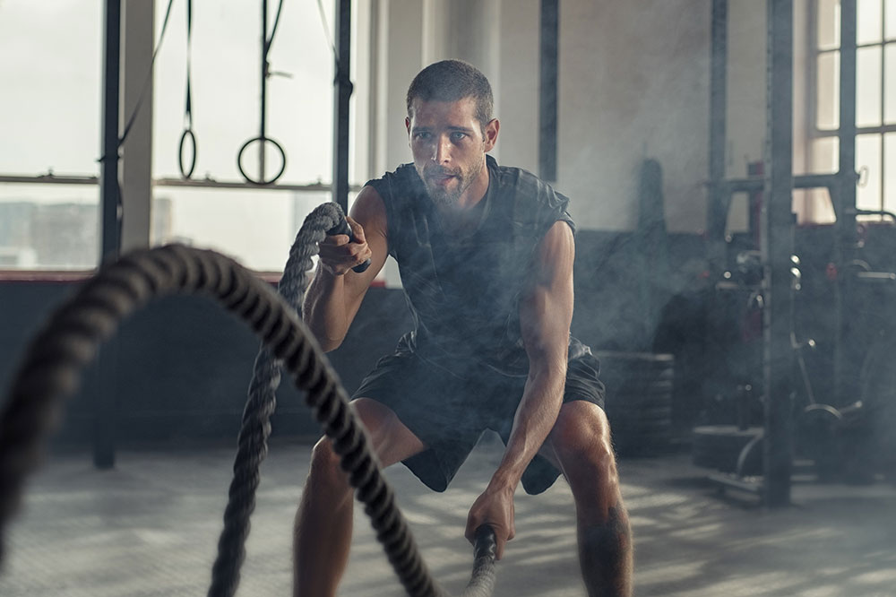 Young-man-exercising-using-battle-rope